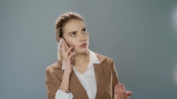 Aufgeaufte Frau im Gespräch auf Handy auf grauem Hintergrund im Studio