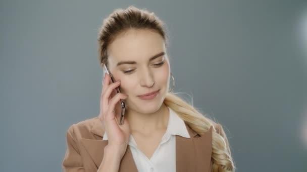 glückliche Geschäftsfrau beschwichtigend Handy. Lächelndes Mädchen mit Smartphone