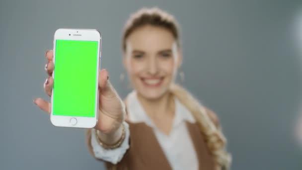 Geschäftsfrau zeigt Handy mit grünem Bildschirm im Studio