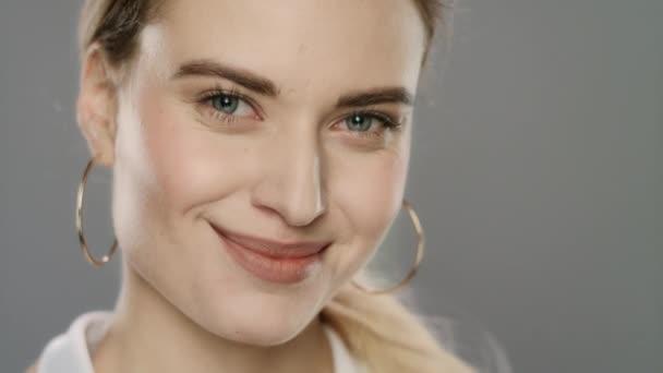 Portré boldog nő mosolygott, és keresi a kamera szürke háttér