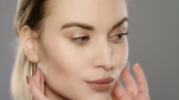 Beauty model touching face skin in slow motion. Close up of young woman face