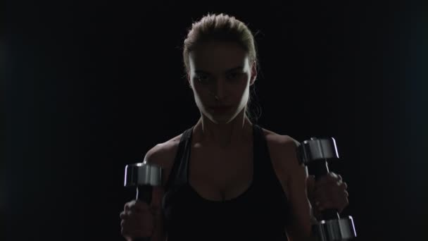 Mosolyogva nő gyakorló súlyzók az edzőteremben. Fit lány mosolyogva során sport edzés
