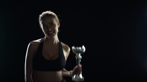 Excited woman holding in hands champion cup on black background. Sport victory
