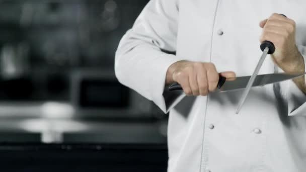 Kochhände schärfen Messer in Zeitlupe. Nahaufnahme Hände kochen Essen in der Küche.