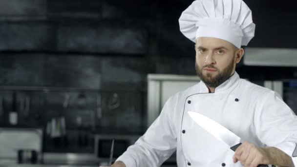 männlicher Koch posiert mit gekreuzten Messern. Koch schärft Messer in der Küche.
