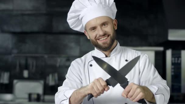 Ember szakács szórakozni késsel a konyhában. Mosolygós séfezés keresztbe kések