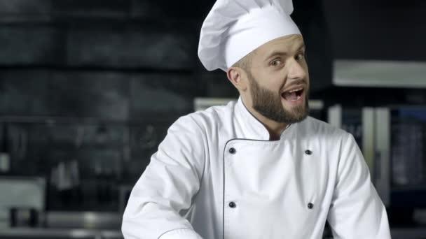 Kochmann posiert in der professionellen Küche. Profi-Koch mit erhobenem Daumen