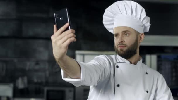 Séf fotót készítünk a konyhában. Portréja Chef figyelembe selfie mobiltelefonon.