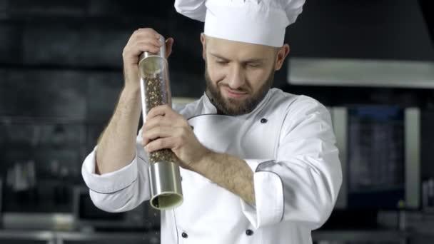 Küchenchef Mann beim Kochen in Küche Restaurant. Männlicher Koch würzt Essen in der Küche.