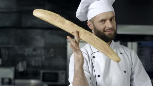 Koch macht Spaß mit französischem Brot in der Küche. Nahaufnahme Mann Hände spielen mit Brot.