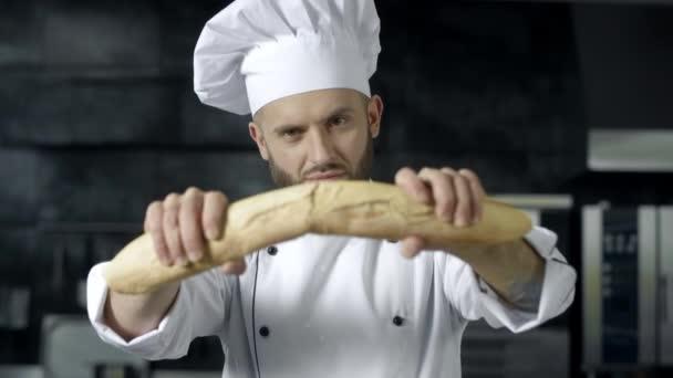 Ein männlicher Koch bricht in Zeitlupe französisches Brot. Nahaufnahme Hände brechen Brot.
