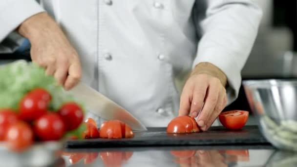Šéfkuchař má v restauraci kuchyňský rajčí. Closeup kuchař vaření čerstvých potravin.