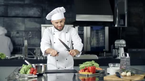 Šéfkuchař v profesionální kuchyni. Vaření s noži na ostření