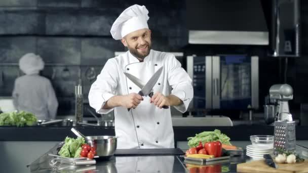 Chef ember készül főzni a konyhában étterem. Férfi szakács, késsel pózol