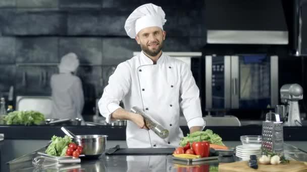 Usměvavý kuchař si hraje s peperboxu na pracovišti. Šťastný pracovník připravuje vaření