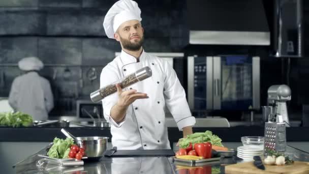 Koch posiert im Küchenrestaurant. Koch wärmt sich mit Pfefferbox am Arbeitsplatz auf.