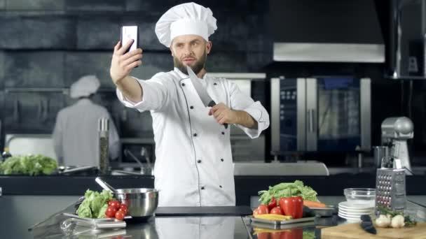 Šéfkuchař dělá fotky v kuchyni. Kuchař s nožem v mobilním telefonu.