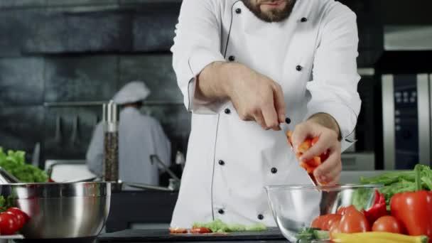 Kuchařský salát v kuchyni. Šéfkuchař dává čerstvou zeleninu do skleněné mísy