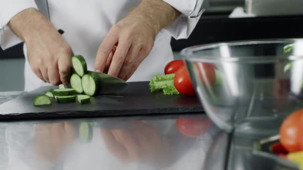 Küchenchef schneidet Gurke im Restaurant. Chef bereitet von Hand frischen Salat zu