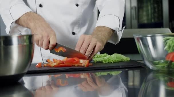 Koch kocht Gemüse in der Küche. Nahaufnahme Hände schneiden Bio-Lebensmittel