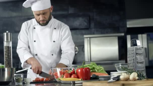 Koch kocht in der Restaurantküche. Profi-Koch macht frischen Salat.