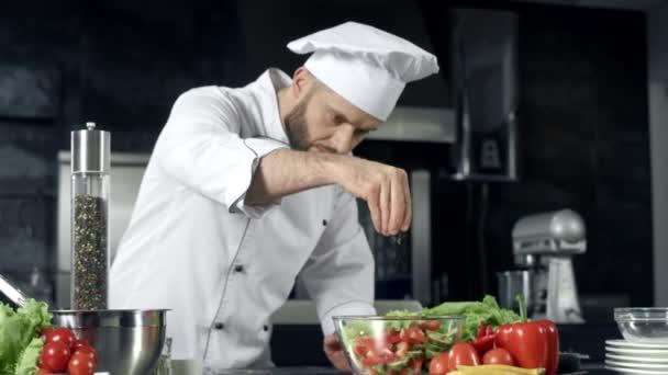 Koch würzt Gemüse in Zeitlupe. Koch kocht frische Lebensmittel in der Küche.
