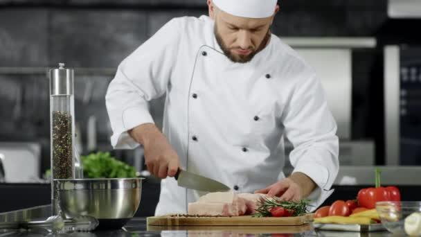 Šéfkuchař řeže vepřový filé v kuchyni. Šéfkuchař připravuje maso v pomalém pohybu