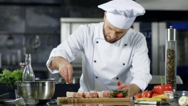 Mužský šéfkuchař, který v kuchyni saluje maso v pomalém pohybu. Kuchyňské nádobí pro profesionální muže