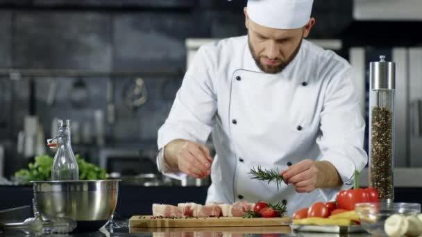 Férfi séf fűszerkeverék húst lassítva. A szakács arcképe hússzelet