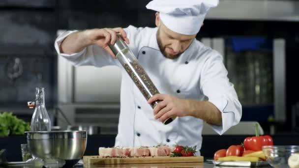 männlicher Koch, der in der Küche Fleisch würzt. Großaufnahme Koch pfeffert Steak am Arbeitsplatz