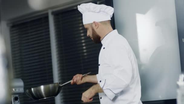 Koch kocht im Wok in der Küche Restaurant. Mann kocht asiatisches Essen in Pfanne