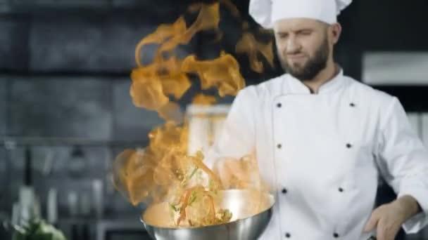 Šéfkuchař vaří v pánvi s ohněm v pomalém pohybu v kuchyni. Mladý kuchař