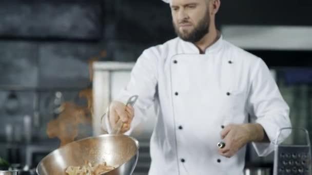 Kuchař vaří v pomalém chodu s pálením ohně. Soustředěný kuchař házel jídlo