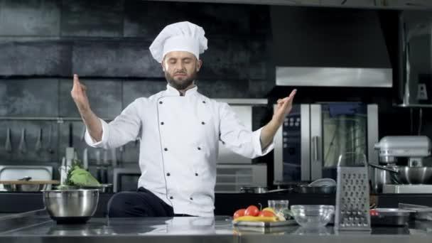 Chef férfi pózol a professzionális konyha. Chef gúnyt a meditáció jelent.