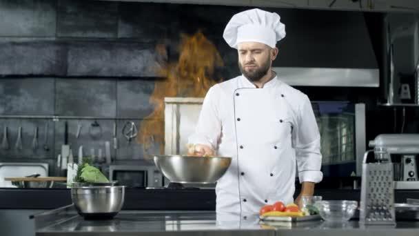 Profi-Koch wirft Essen in Pfanne mit brennender Flamme auf Küche