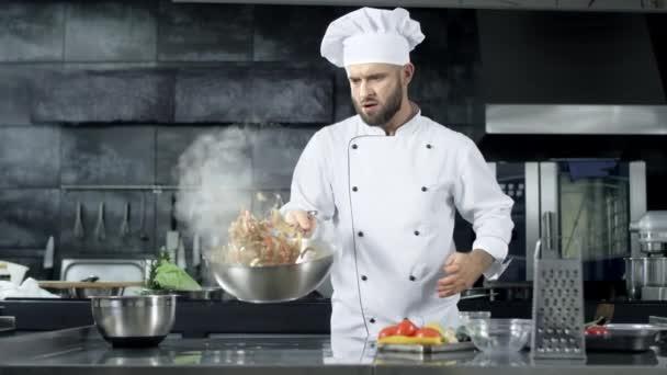 Kuchař vaří v kuchyňském restaurantu. Soustředěný kuchař.