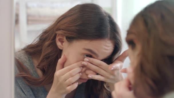 Fókuszált nő elhelyezés a kontaktlencse a szem első fürdőszoba tükör