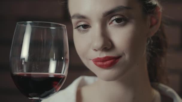 Porträt schöne Frau mit Rotwein im Weinglas posiert und blickt in die Kamera