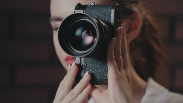 Bella donna scattare foto con fotocamera depoca sullo sfondo muro di mattoni