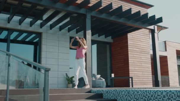 glückliche Frau macht Selfie auf Luxus-Haus. Entspanntes Mädchen macht Handyfoto