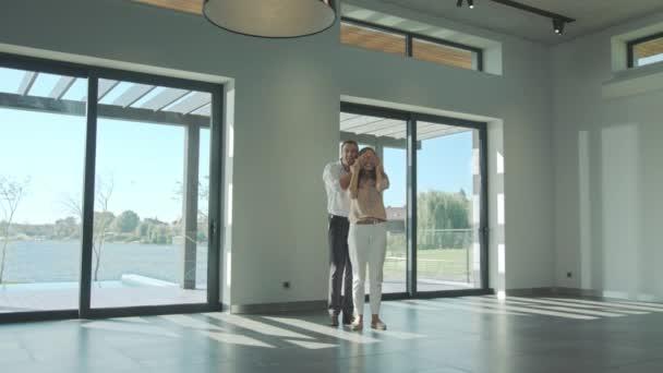 Muž zavírá očima ženu v luxusním domě. Šťastný manžel zobrazující domov překvapení