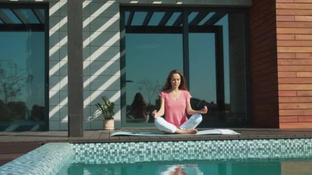 Klidná žena medituje blízko bazénu. Mladá dáma dělá cvičení jóga.