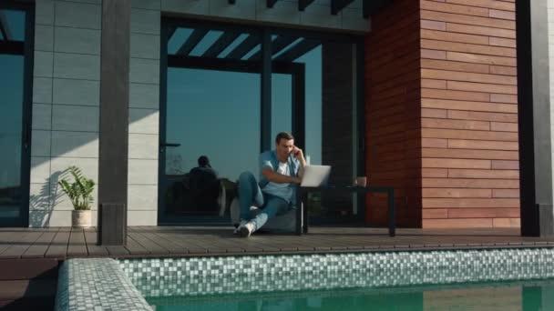 Bohatý muž, který mluví v luxusním domě blízko bazénu.