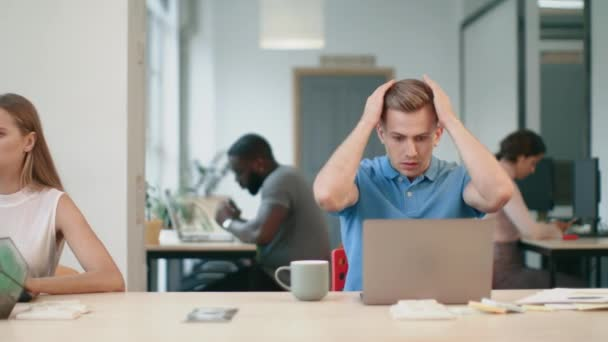 Upset man looking at laptop computer at workplace. Shocked man reading news