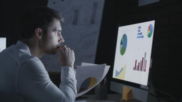 Soustředěný obchodník analyzující finanční dokument v noční kanceláři