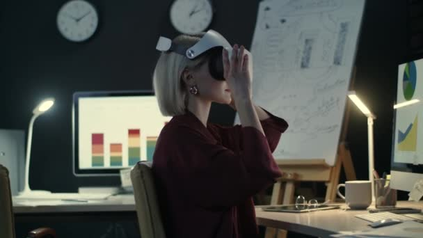 Modern business woman wearing virtual reality glasses in night office