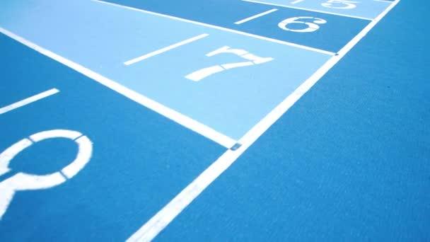 Piste da corsa sportive in colori blu con numeri diversi. Numero di corsie