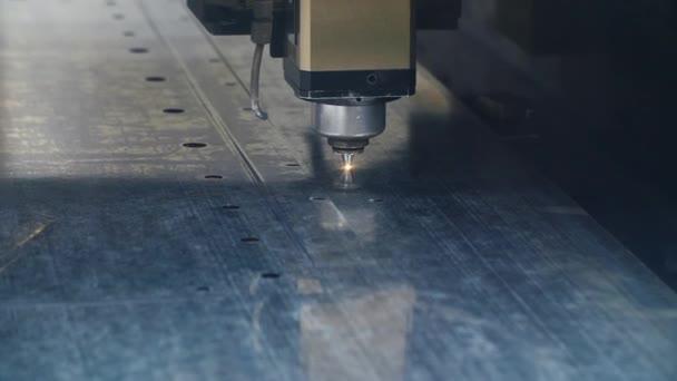 Průmyslové laserové odřezávání děr v kovové plese. Moderní přesné vybavení