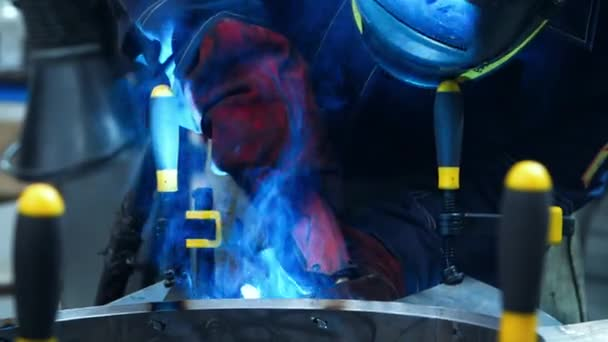 Welding torch nozzle in action close up. Man making weld in workshop