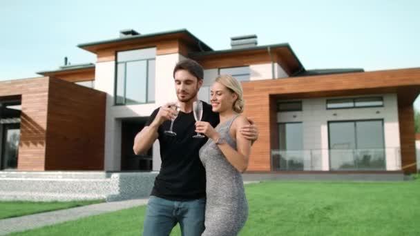 Šťastný pár popíjení šampaňského s téměř luxusním domovem.